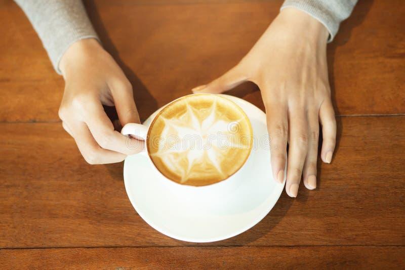 Vrouwelijke handen die kop van koffie met het schuim van de spinnewebvorm over klaar om op rustieke houten lijst te drinken houde stock fotografie