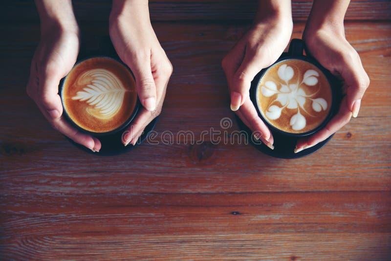 Vrouwelijke handen die koppen van koffie houden stock foto