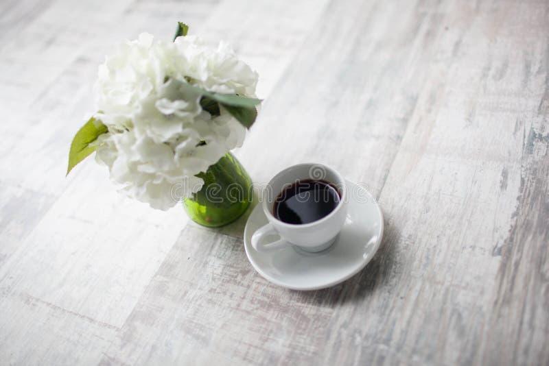 Vrouwelijke handen die koppen van koffie op rustieke houten achtergrond houden stock foto's
