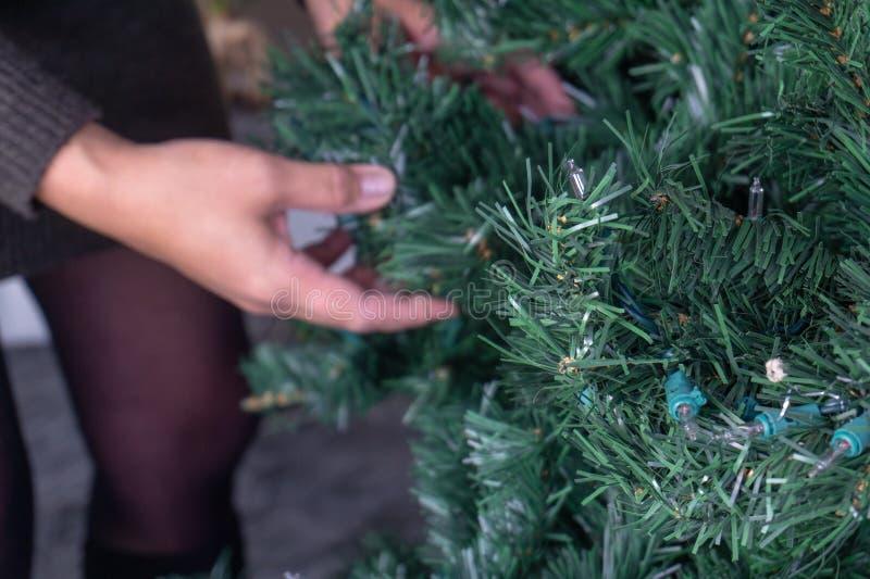 Vrouwelijke handen die kunstmatige Kerstmis ontrafelen royalty-vrije stock afbeelding