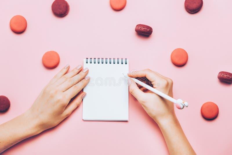 Vrouwelijke handen die in leeg notaboek schrijven op roze achtergrond met vele makarons stock afbeelding