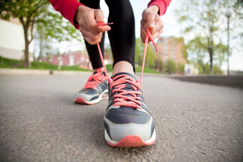 Vrouwelijke handen die loopschoenen rijgen close-up stock foto
