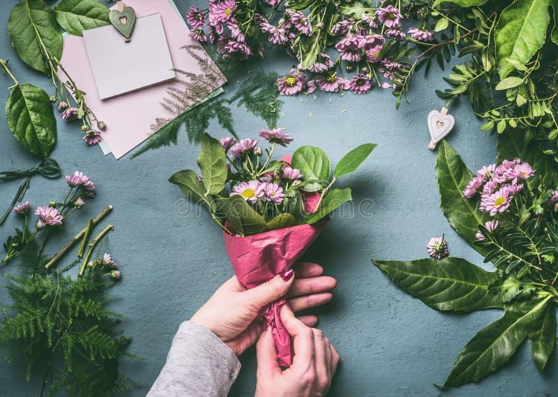 Vrouwelijke handen die mooi boeket van roze bloemen met verpakkend document op bloemistwerkruimte maken stock afbeeldingen