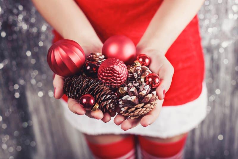 Vrouwelijke handen die rode Kerstmisdecoratie en kegels, glanzende Kerstmisachtergrond houden Vakantiegift en ornamenten toning stock foto