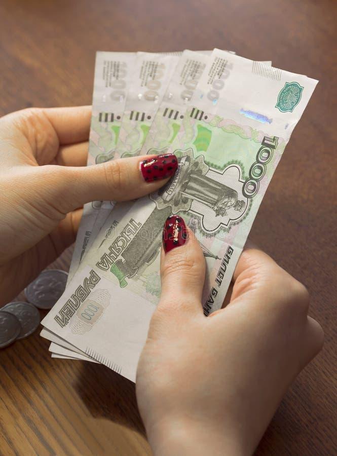 Vrouwelijke handen die Russische bankbiljetten van duizend roebels houden stock afbeelding