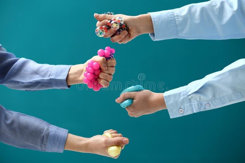 Vrouwelijke handen die spanningsballen op kleurenachtergrond drukken royalty-vrije stock afbeelding