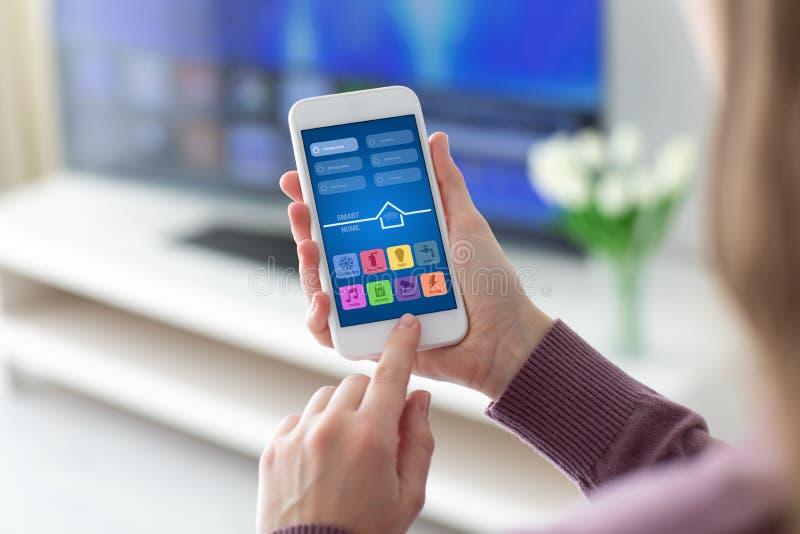 Vrouwelijke handen die telefoon met app slim huis op het scherm houden stock foto's