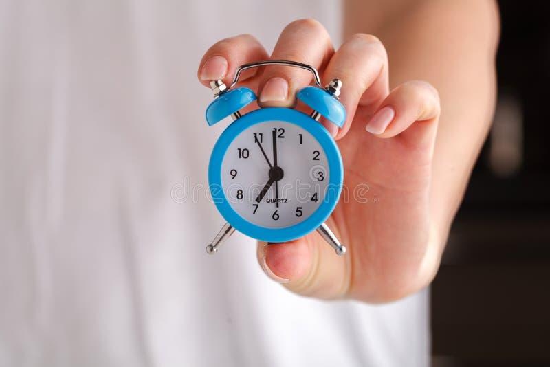 Vrouwelijke handen die wekker houden stock fotografie