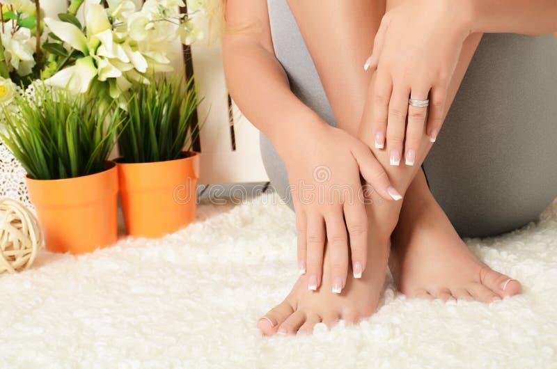 Vrouwelijke handen en voeten met manicure en een pedicure stock foto's