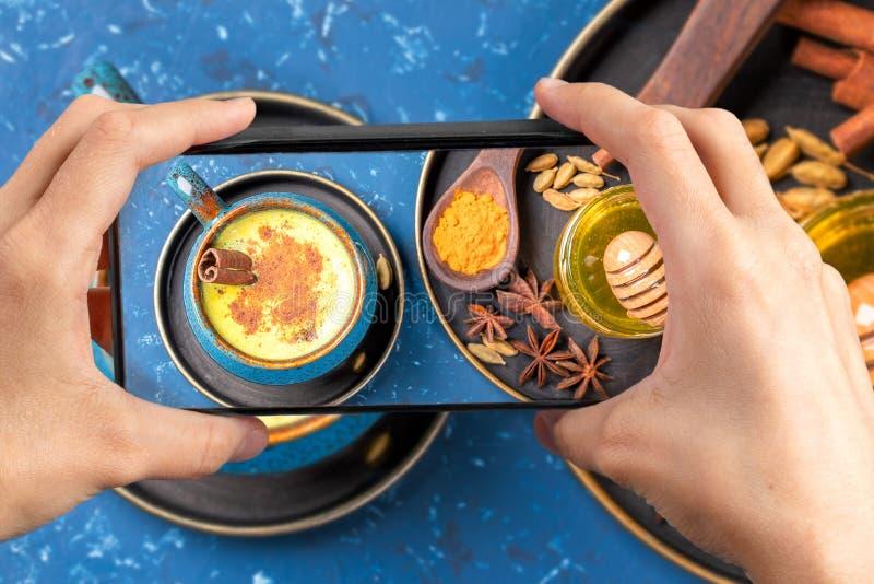Vrouwelijke handen houden smartphone vast met foto van een kopje ayurvedische gouden turmere melk met ingrediënten op blauw Boven royalty-vrije stock foto's