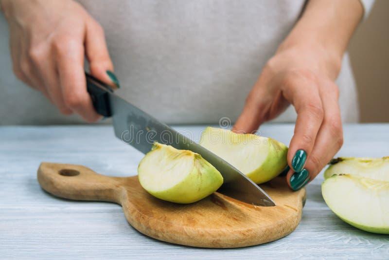 Vrouwelijke handen met een heldere manicure die met een keukenmes gre wordt gesneden stock foto