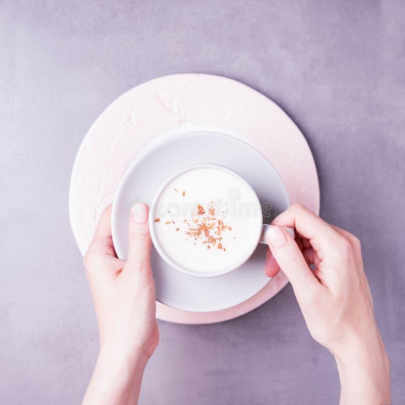 Vrouwelijke handen met een kop van de koffiecappuccino Manicure met naakt nagellak De grijze achtergrond, kopieert ruimte, hoogst stock afbeelding
