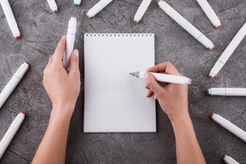 Vrouwelijke handen met een teller Trek in een wit notitieboekje Ruimte voor ontwerp Hoogste mening royalty-vrije stock fotografie