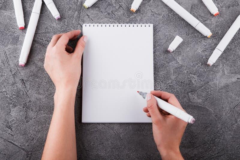 Vrouwelijke handen met een teller Trek in een wit notitieboekje Ruimte voor ontwerp Hoogste mening stock foto's