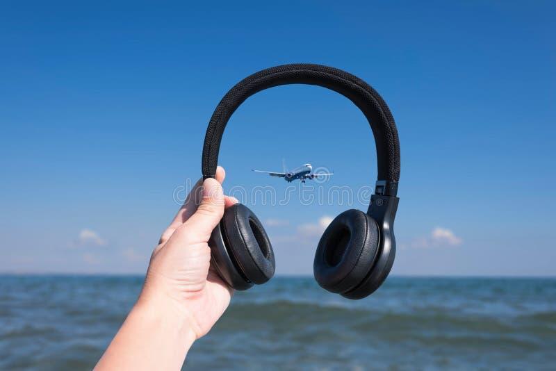 Vrouwelijke handen met hoofdtelefoons op de overzeese golf en de landende vliegtuigachtergrond stock foto