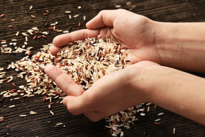 Vrouwelijke handen met hoop van verschillende ruwe rijst, close-up stock afbeeldingen
