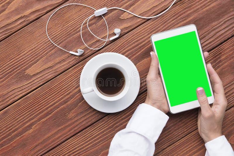 Vrouwelijke handen met kop van koffie en model digitale tablet en hoofdtelefoons op bruin houten bureau Zoete croissant en een ko royalty-vrije stock afbeeldingen