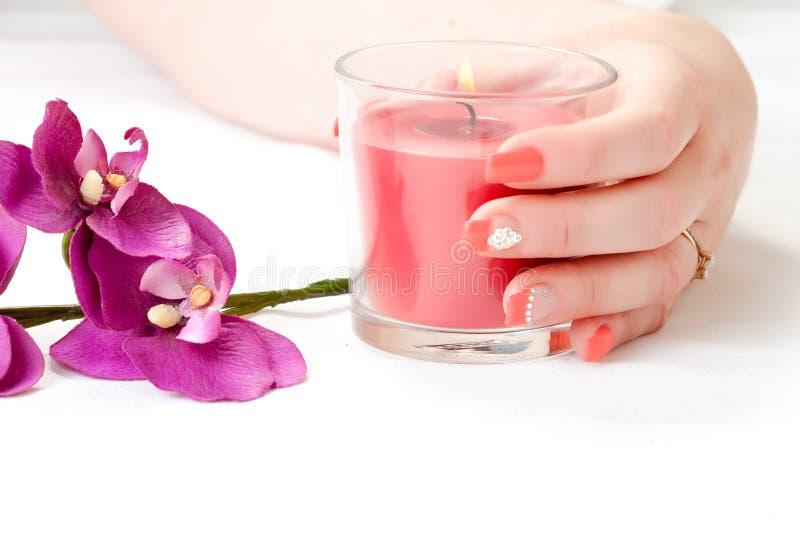 Vrouwelijke handen met orchideebloemblaadjes, kaars en spijkerart. stock afbeeldingen