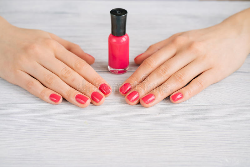 Vrouwelijke handen met rode manicure en nagellakfles op een woode stock fotografie
