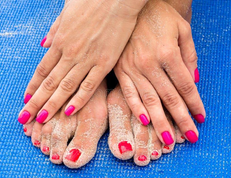 Vrouwelijke handen met rode manicure op vrouwelijke benen met een rode pedicur royalty-vrije stock foto