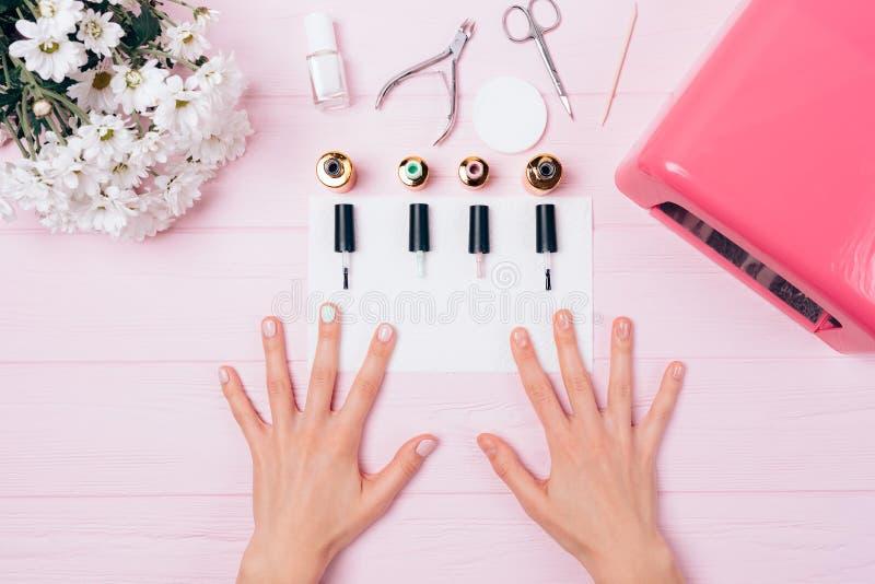 Vrouwelijke handen met schellak die dichtbij geopende flessen behandelen stock fotografie
