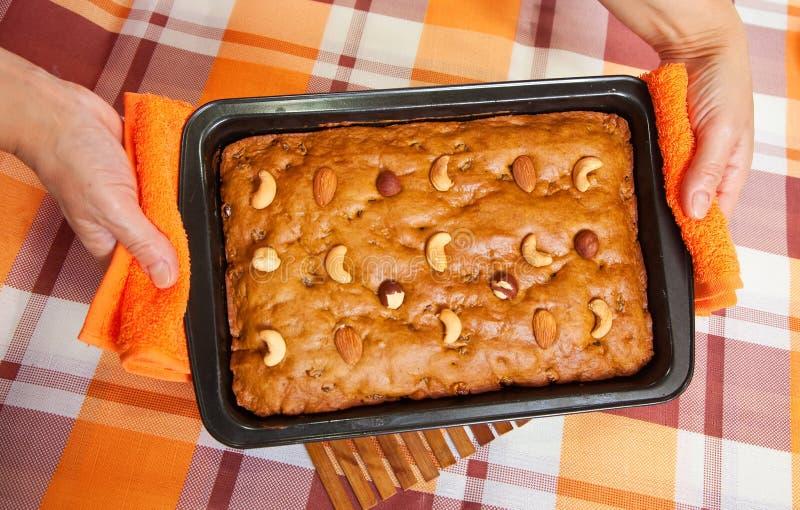 Vrouwelijke handen met verse honingscake stock afbeeldingen
