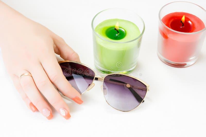 Vrouwelijke handen met zonglazen, kaarsen en spijkerart. royalty-vrije stock afbeelding