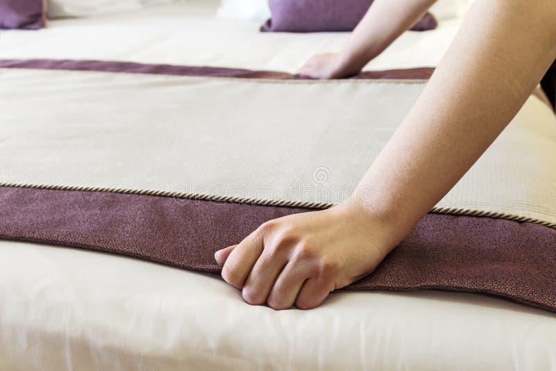 Vrouwelijke handen verbeterde deken op het bed stock fotografie