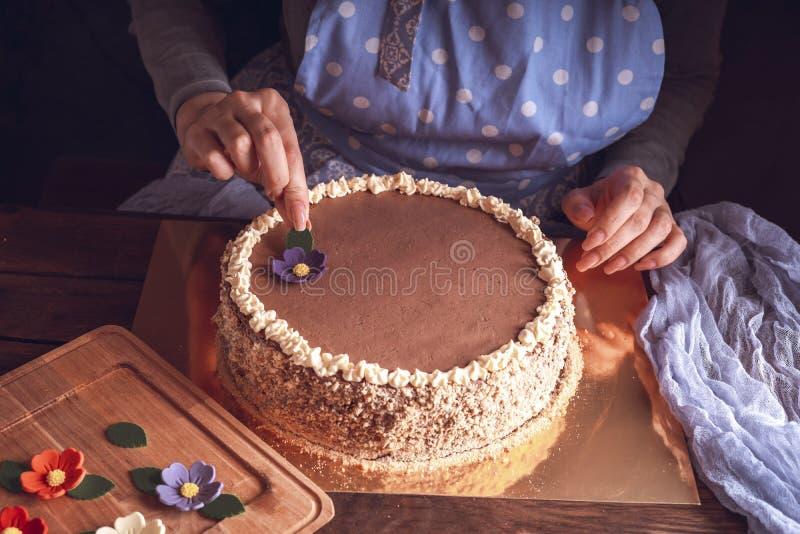Vrouwelijke handen versieren kiev-cake voor thuisgebruik stock foto