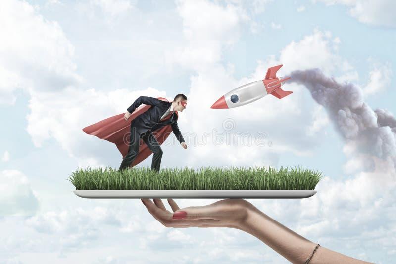 Vrouwelijke het grasraad van de handholding met kleine zakenman in rood supermanmasker en mantel met zilveren rode raket op blauw royalty-vrije stock fotografie