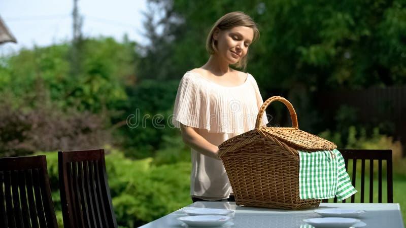 Vrouwelijke het plaatsen rieten picknickmand op lijst, openluchtpicknick in buitenhuis royalty-vrije stock afbeelding