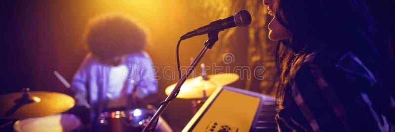 Vrouwelijke het spelen piano door slagwerker in nachtclub stock foto's