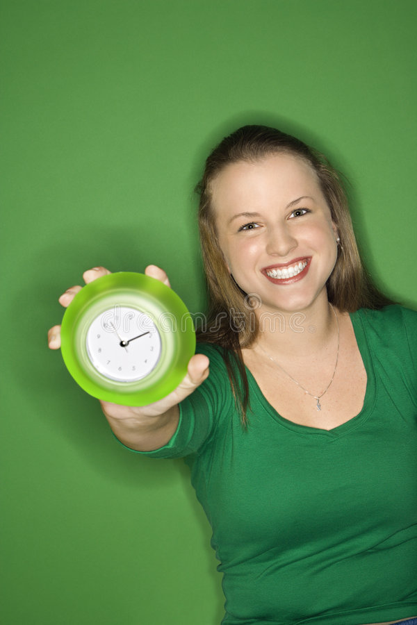 Vrouwelijke het standhouden klok. stock foto