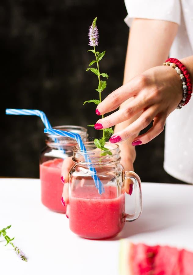Vrouwelijke het toevoegen munttak aan watermeloen smoothie stock afbeelding