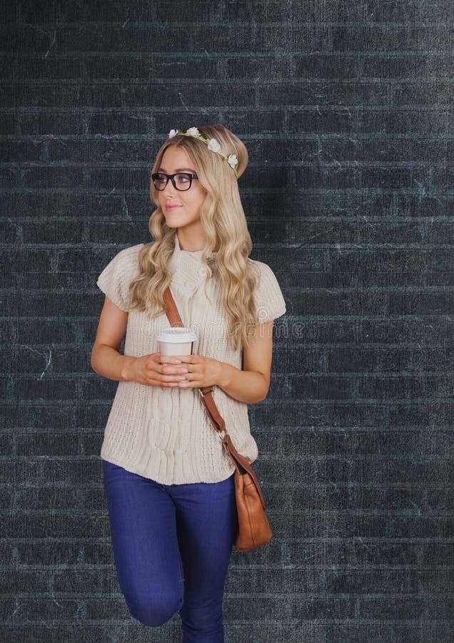 Vrouwelijke hipster die beschikbaar glas houden tegen muur stock afbeeldingen