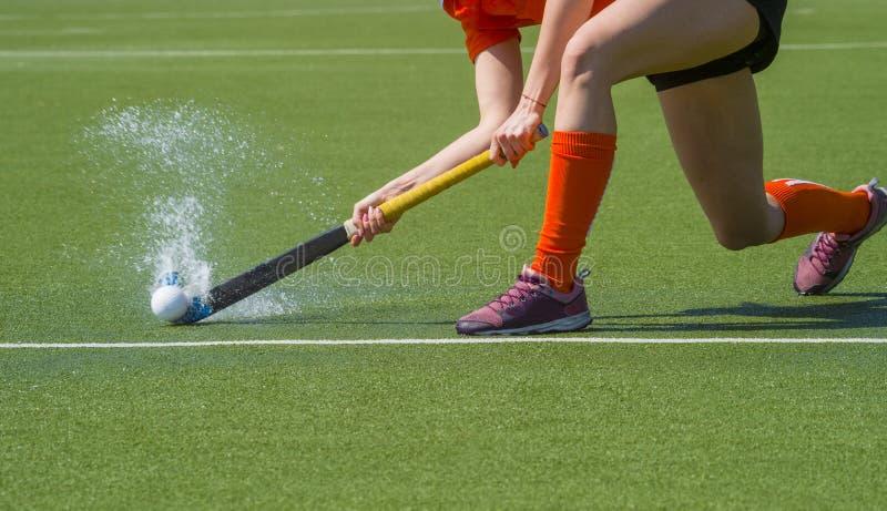 Vrouwelijke hockeyspeler die tot een teampartner overgaan op een gebied van moderne, water kunstmatig astroturf stock afbeeldingen