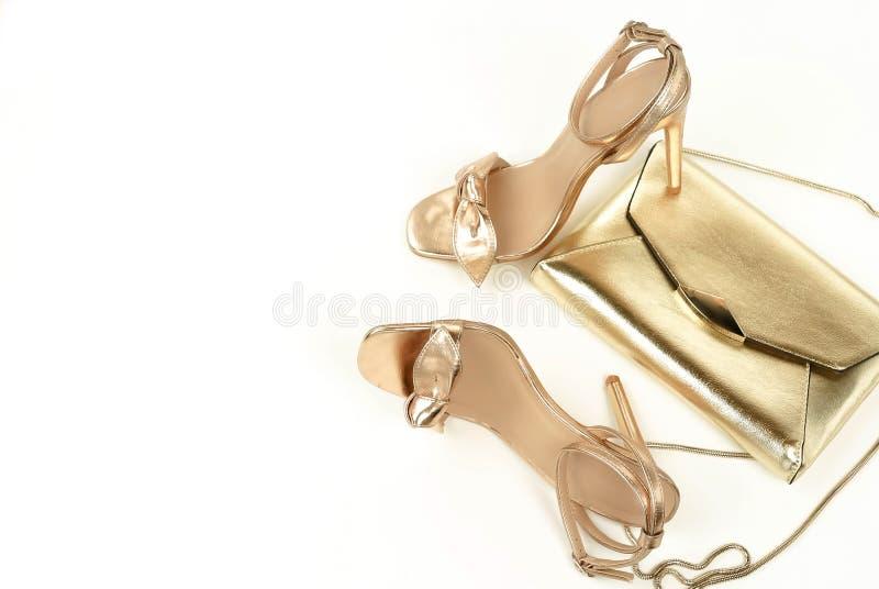 Vrouwelijke hoge sandals gouden kleur en handtas van hielschoenen stock fotografie