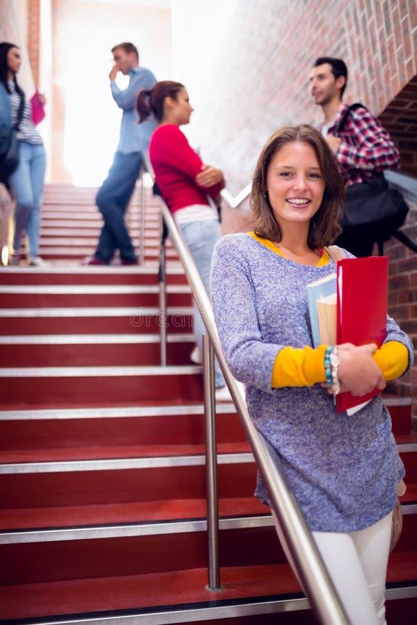 Vrouwelijke holdingsboeken met studenten op treden in universiteit stock afbeeldingen