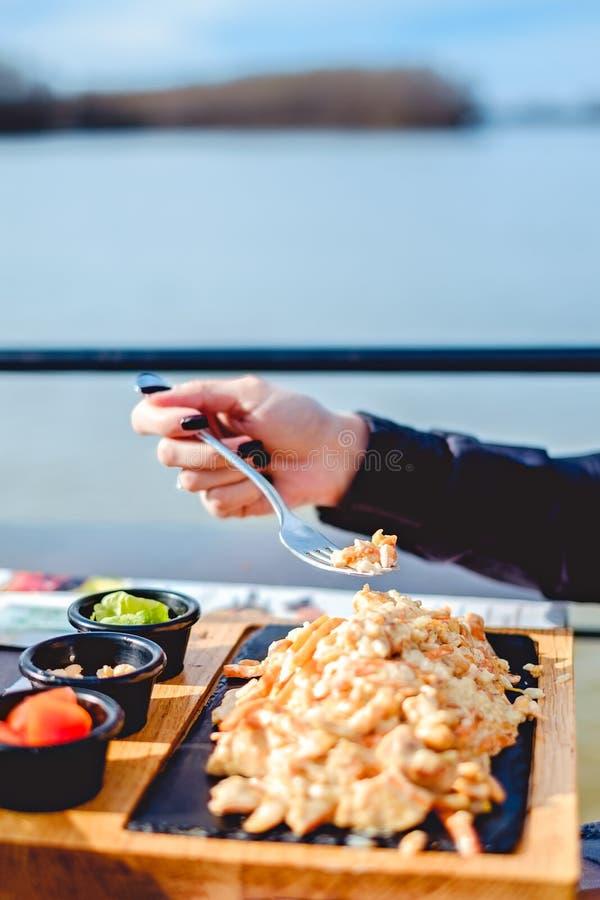Vrouwelijke holdingsvork boven kip met pinda en rijst stock afbeeldingen