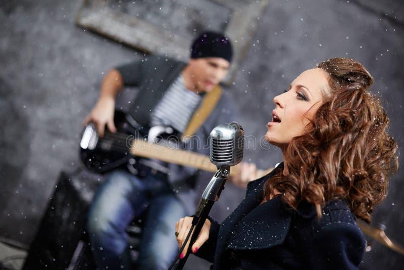 Vrouwelijke hoofdvocalist en gitarist in studio stock afbeeldingen