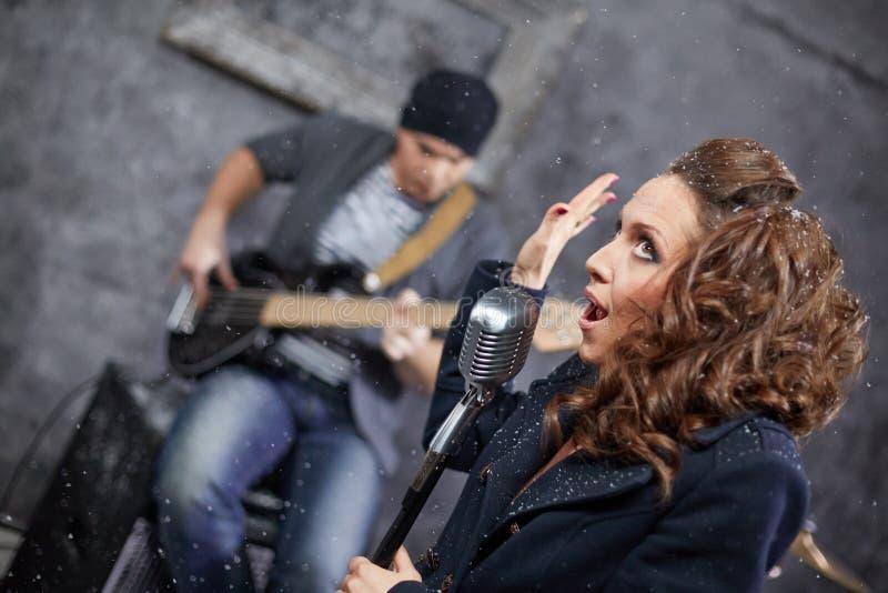 Vrouwelijke hoofdvocalist en gitarist in studio royalty-vrije stock fotografie