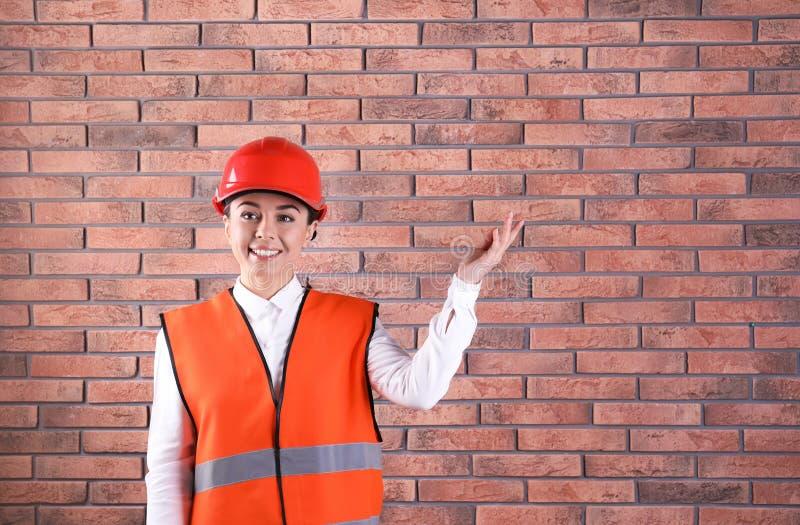 Vrouwelijke industriële ingenieur in eenvormig op muurachtergrond, ruimte voor tekst De apparatuur van de veiligheid royalty-vrije stock foto's