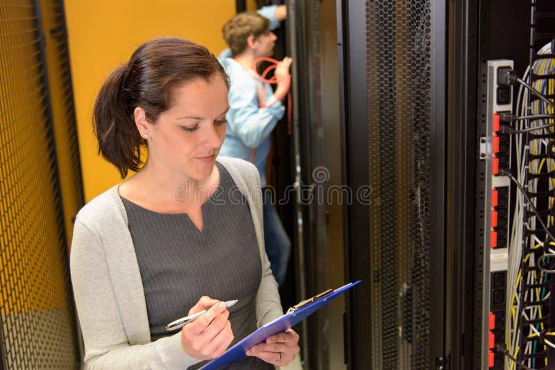 Vrouwelijke ingenieur in datacenter stock foto's
