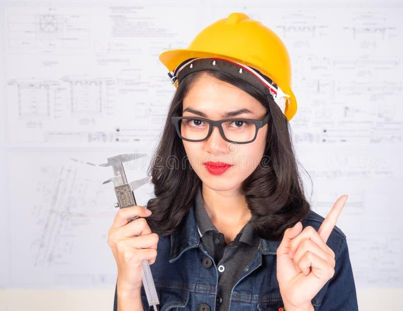Vrouwelijke ingenieur die een meetinstrument met een blauwdruk houden als achtergrond royalty-vrije stock foto