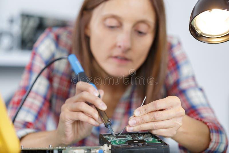 Vrouwelijke ingenieur die gebroken computer harde aandrijving bevestigen royalty-vrije stock foto
