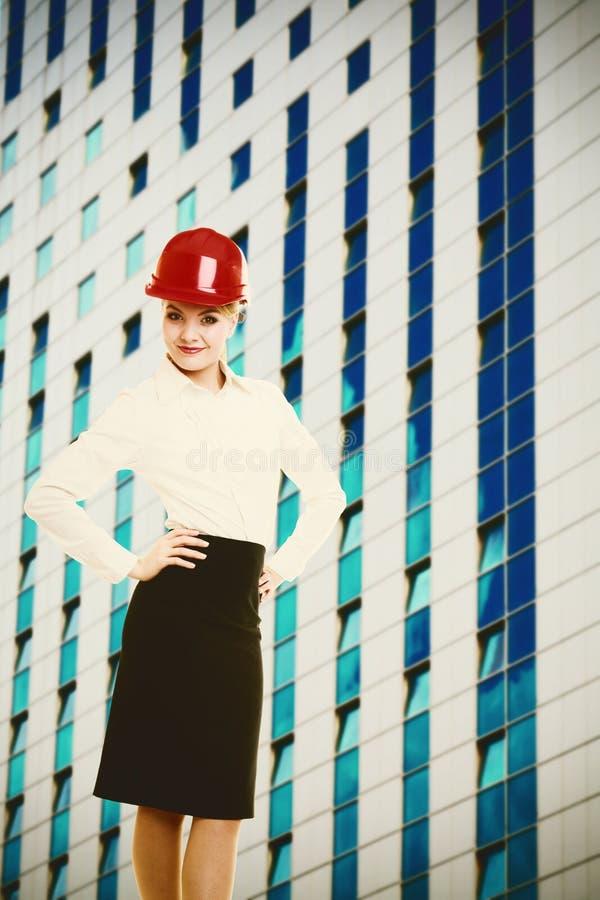 Vrouwelijke ingenieursvrouw in rode veiligheidshelm en de moderne bouw stock afbeelding
