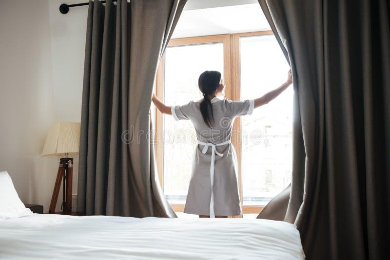 Vrouwelijke kamermeisje het openen venstergordijnen in de hotelruimte royalty-vrije stock afbeeldingen