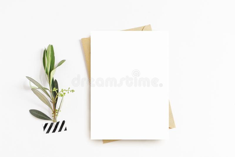 Vrouwelijke kantoorbehoeften, de scène van het Desktopmodel Lege groetkaart, ambachtenvelop, washiband en met olijftak wit stock afbeeldingen