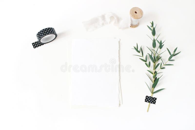 Vrouwelijke kantoorbehoeften, het modelscène van de huwelijksdesktop Lege groetkaart, envelop, zwarte washiband, zijdelint en royalty-vrije stock afbeeldingen