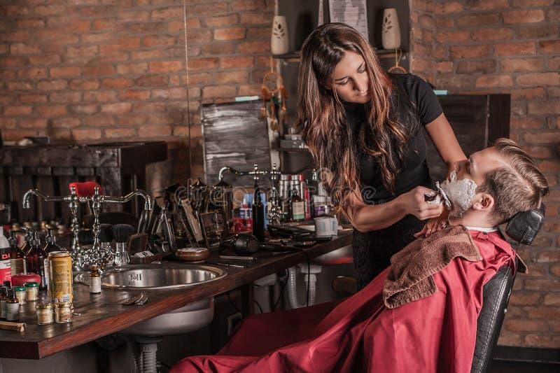 Vrouwelijke kapper die een cliënt in een kapperswinkel scheren royalty-vrije stock foto
